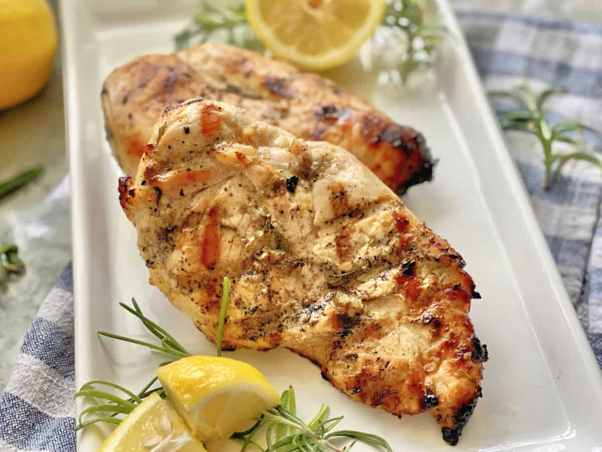Close up of grilled chicken breast on white plate with fresh rosemary and lemon.