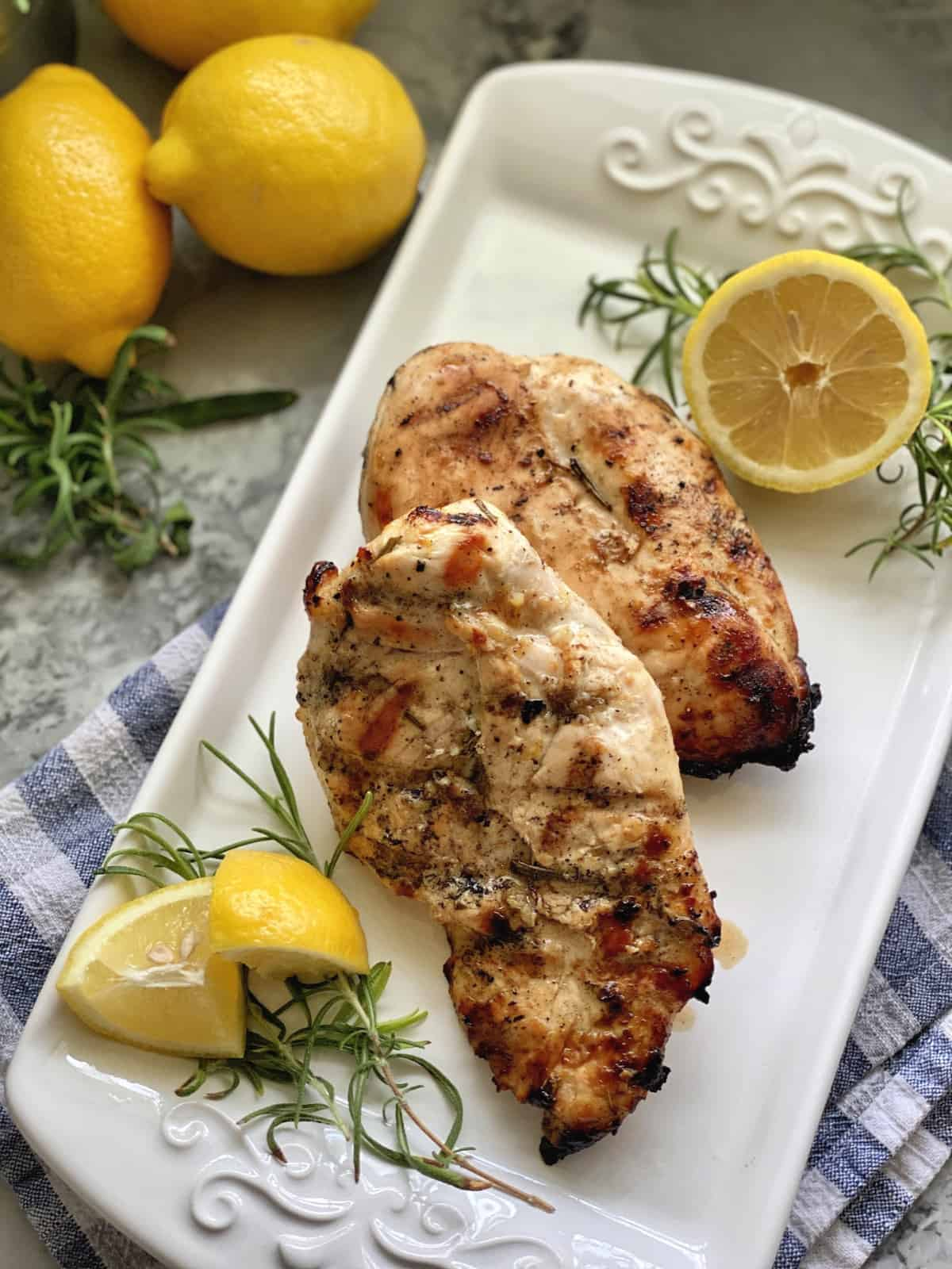 Top view of grilled chicken breast on a white platter with fresh lemon and rosemary.