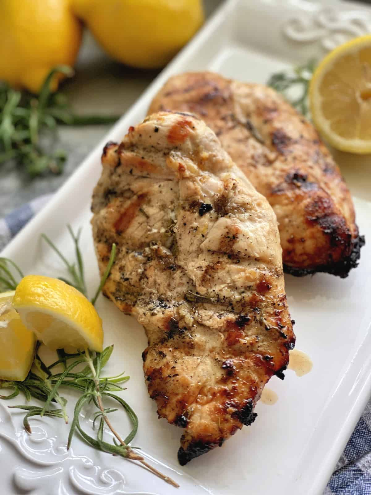 Grilled chicken breast on a white platter with fresh lemon wedges and rosemary sprigs.