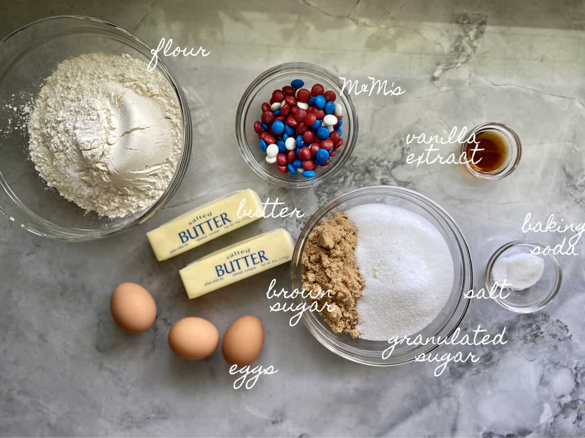 Ingredients on marble counter: flour, sugar, butter, eggs, M&M's, salt, baking soda, vanilla extract.