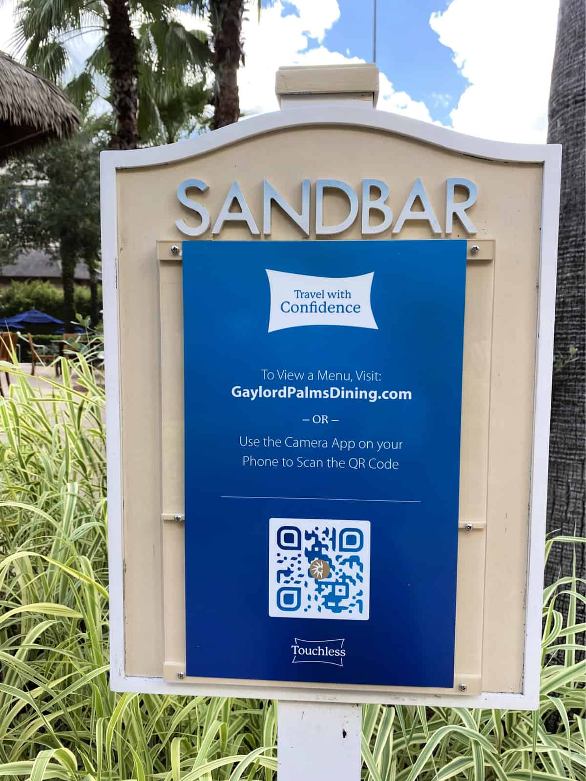 Sandbar travel with confidence sign that has a dining menu qr code.