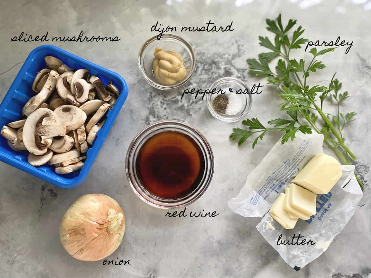 Ingredients on marble counter: mushrooms, onions, red wine, mustard, parsley, butter.