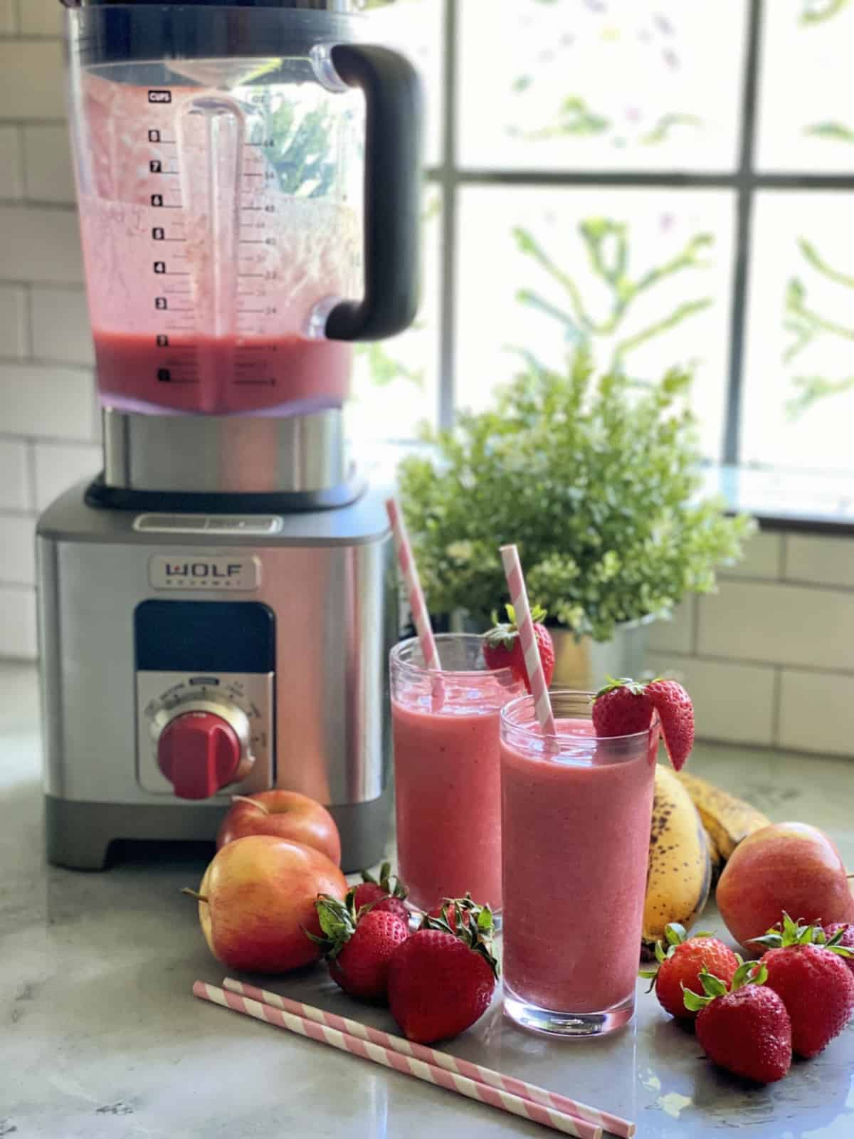 Two glasses with smoothies next to a blender with fruit on the counter.