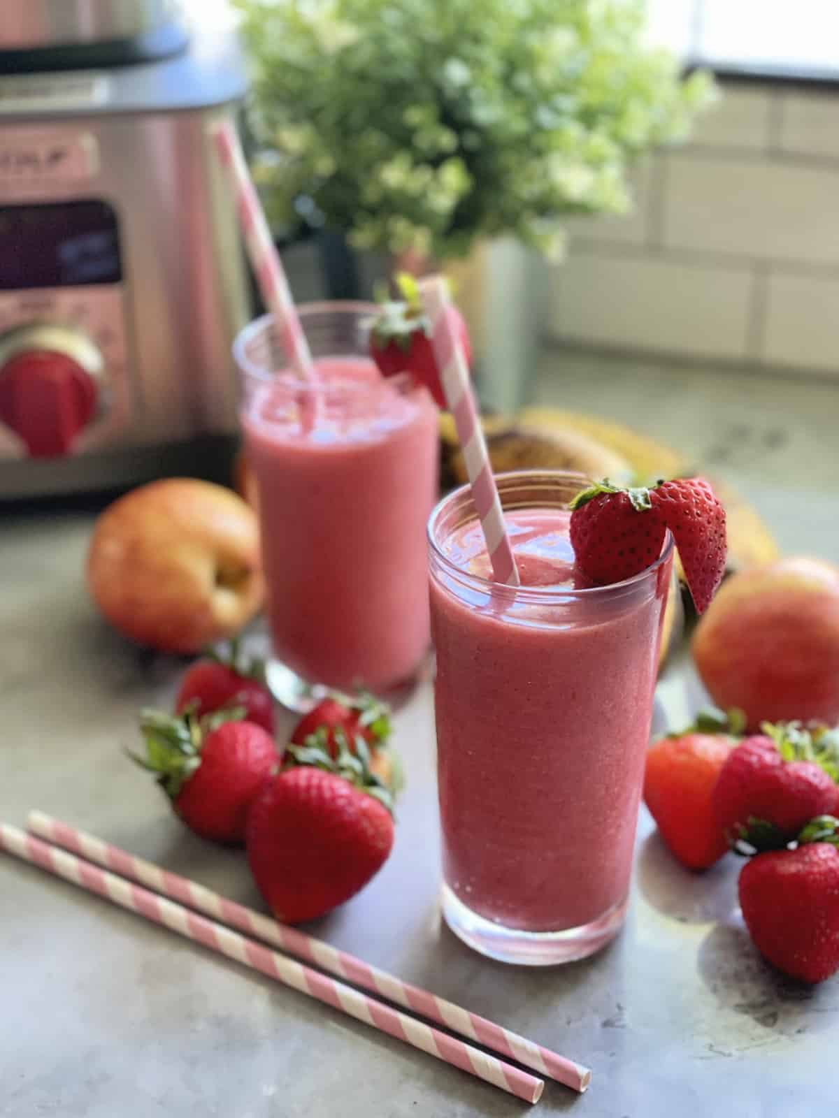 Stawberry smoothie in a glass with fresh strawberries  and paper straws around glass.