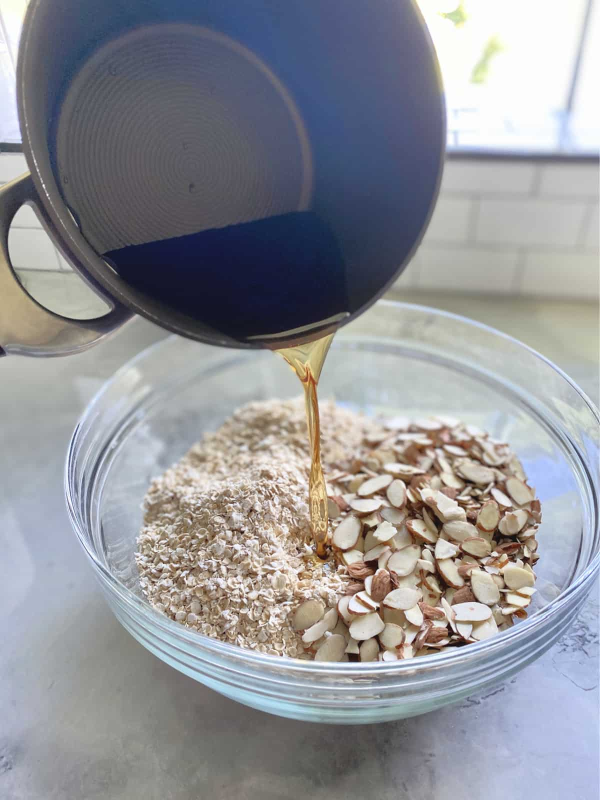 Pot pouring brown liquid into a glass bowl of oats and almond slices on a marble countertop.