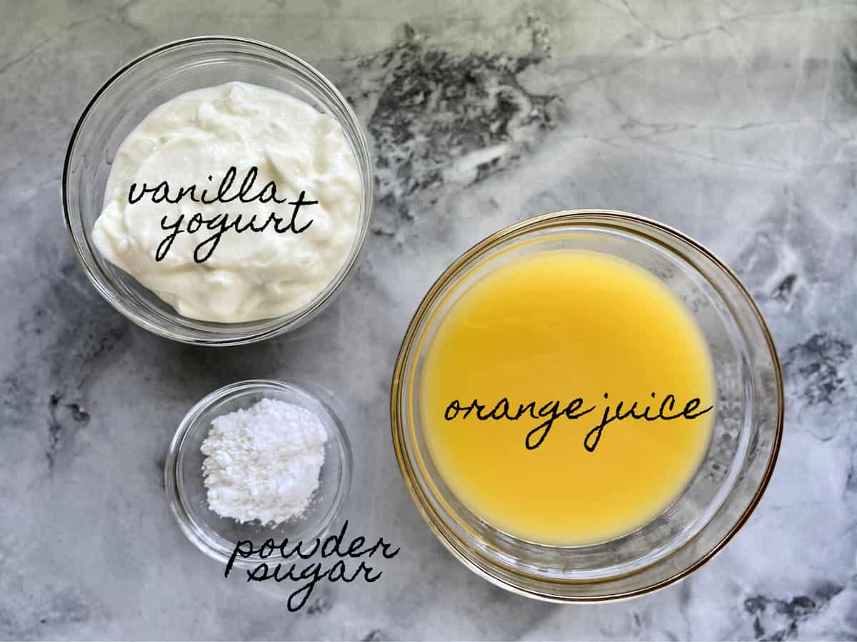 Ingredients on marble counter in glass bowls; vanilla yogurt, powder sugar, and orange juice.
