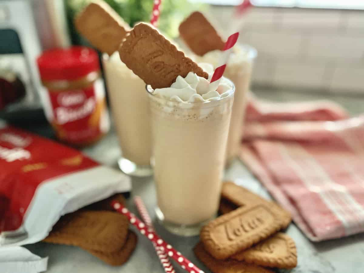 Three glasses bundled together with light brown milkshake, whipped cream, and cookies.