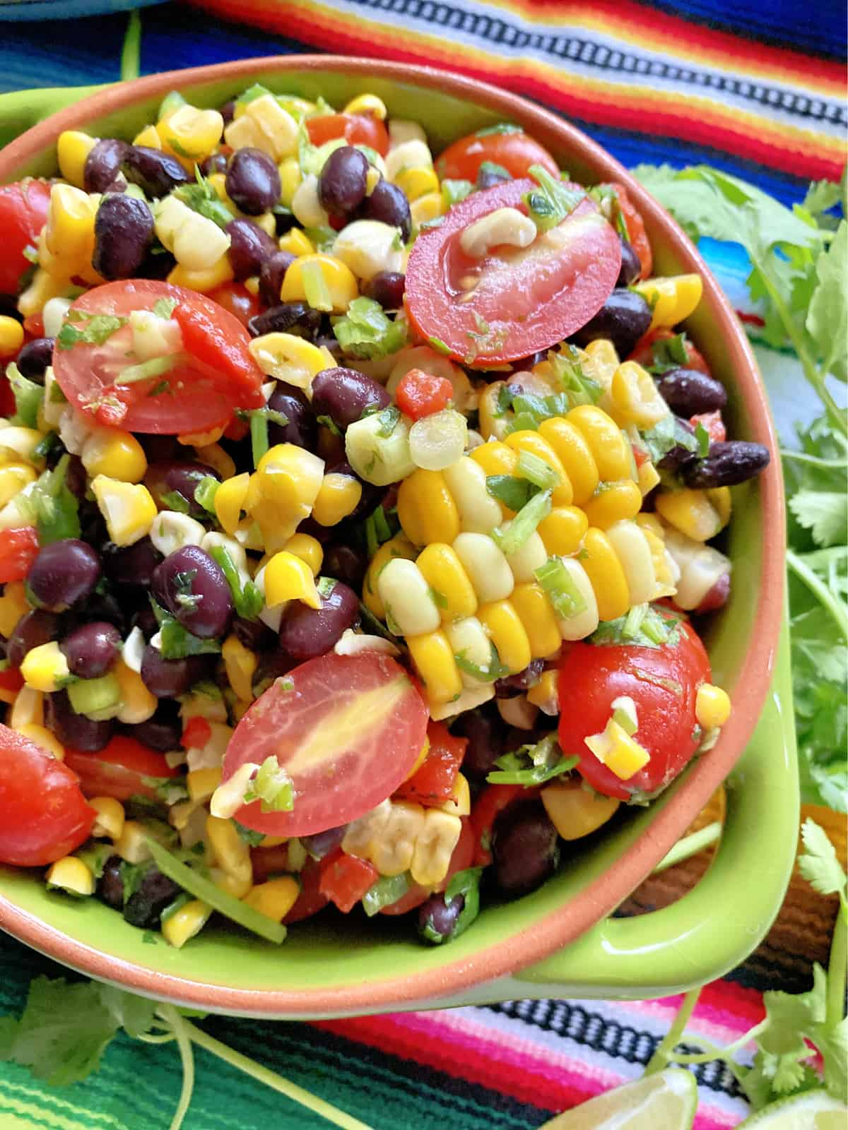 Top view of a green bowl filled with corn kernels, sliced grape tomatoes, cilantro, and black beans.