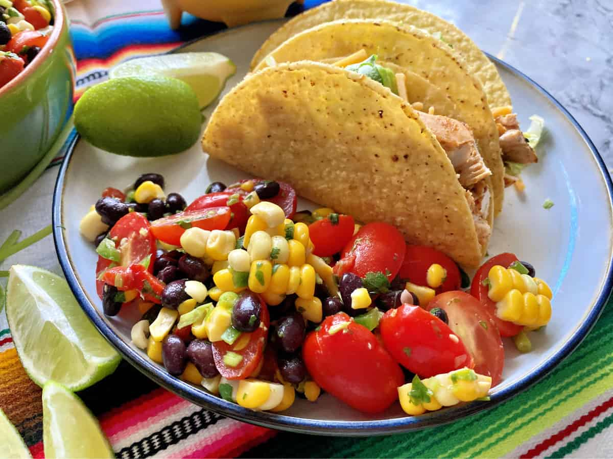 White plate with corn, black beans, and tomatoes next to chicken tacos and lime.