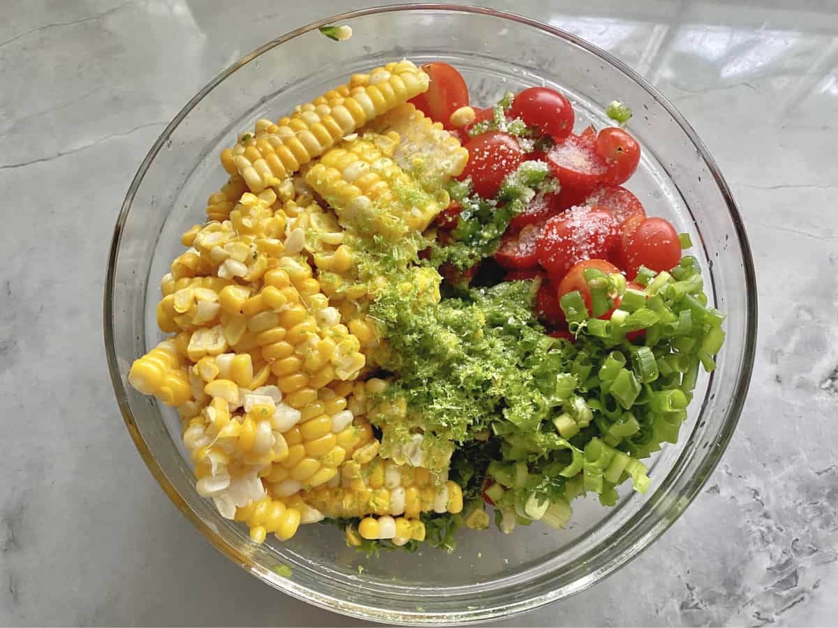 Top view of a glass bowl with corn kernels, sliced tomatoes, salt, green onions, and lime zest.
