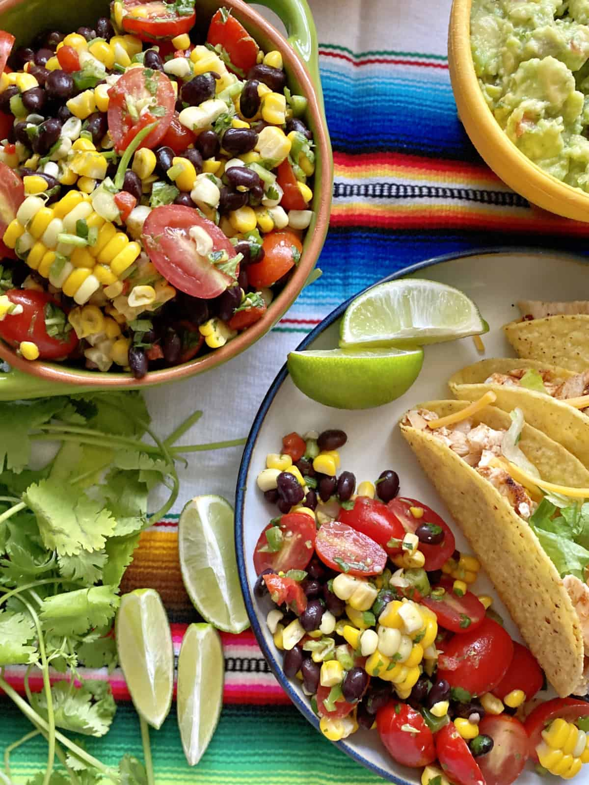 Top view of corn, black beans, and tomatoes on a plate with tacos and lime.