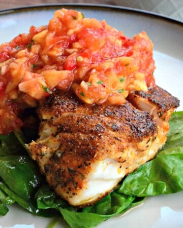 Blackened snapper with peach salsa on top all resting on a bed of spinach.