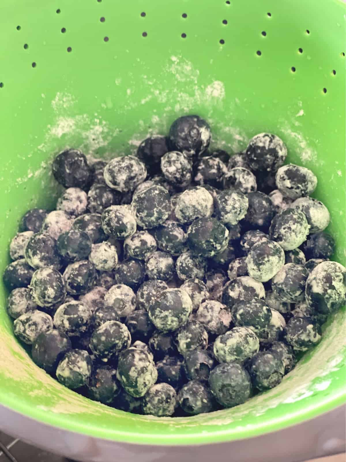 Floured blueberries in a neon green colander.