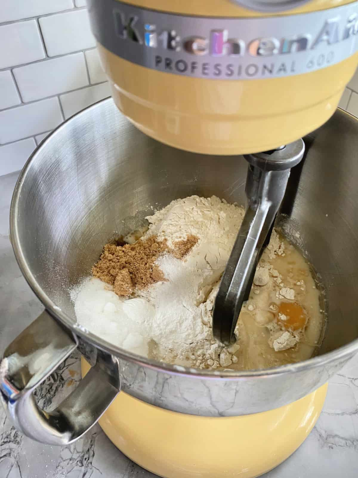Dry and wet ingredients in a stainless steel mixing bowl attached to a KitchenAid Yellow Mixer.