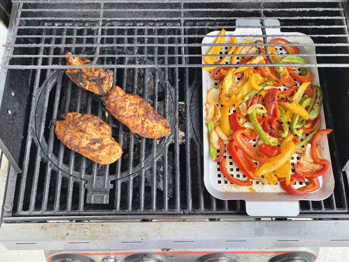 Chicken on a grill next to a grill pan full of multi-color bell peppers and onion.