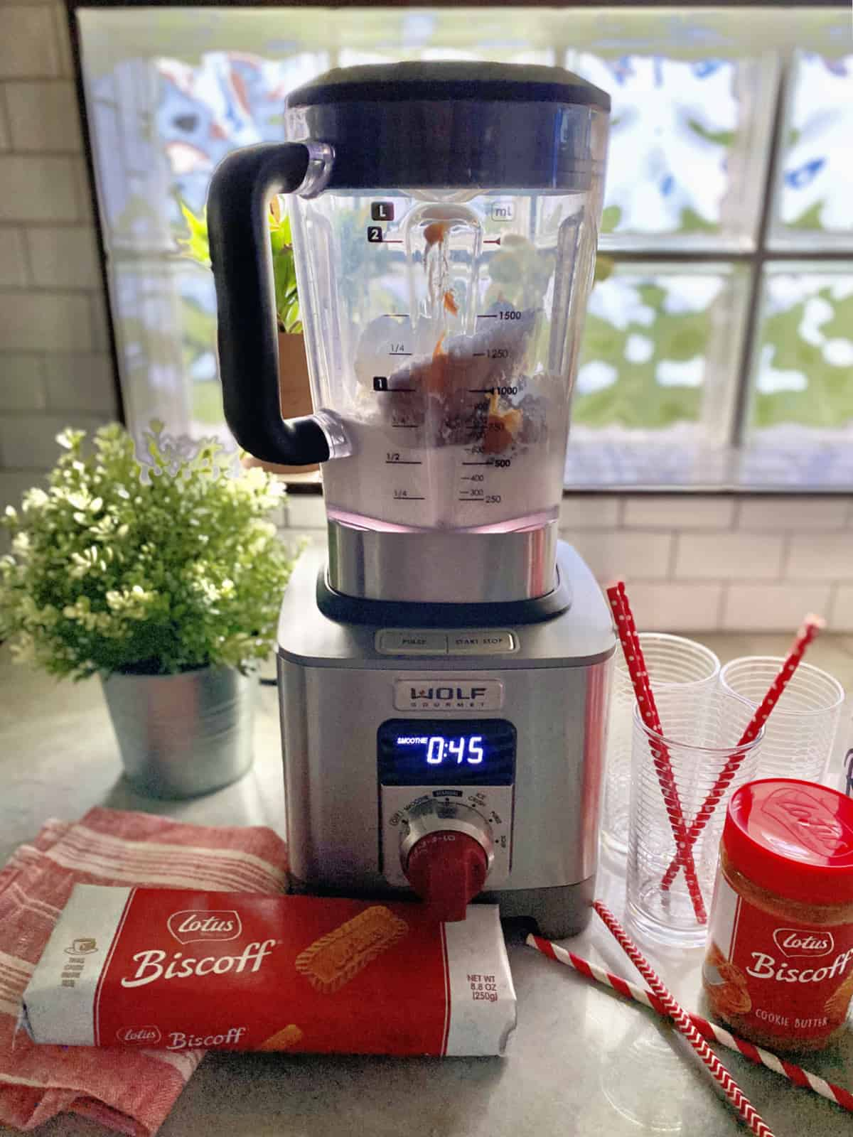 Blender set to to 45 seconds filled with whipped cream and cookie spread with cookies on counter.