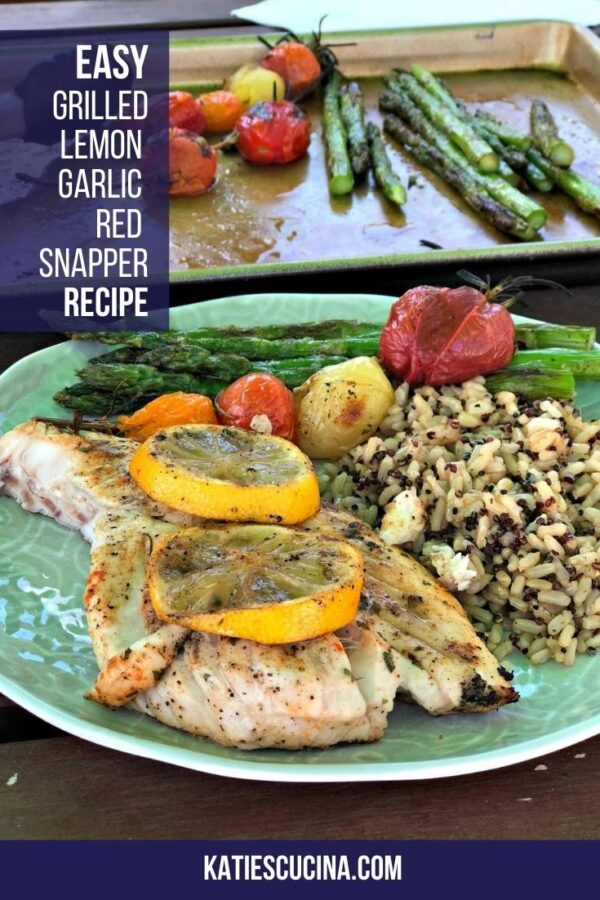 Fish with lemon on a green plate with rice and veggies.