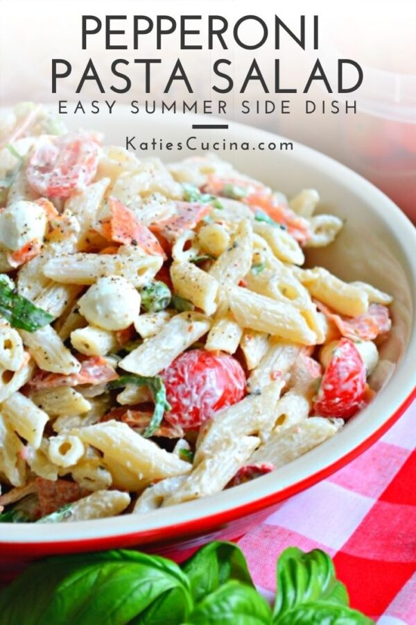 Creamy penne pasta salad with tomatoes and basil text on image for Pinterest.