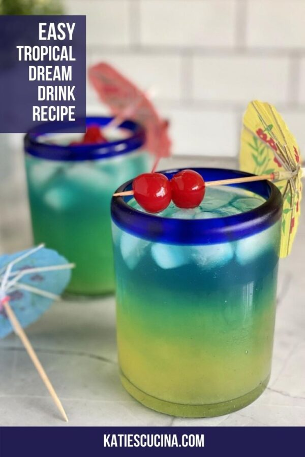 Two yellow, green, blue layered drinks with 2 maraschino cherries on top.