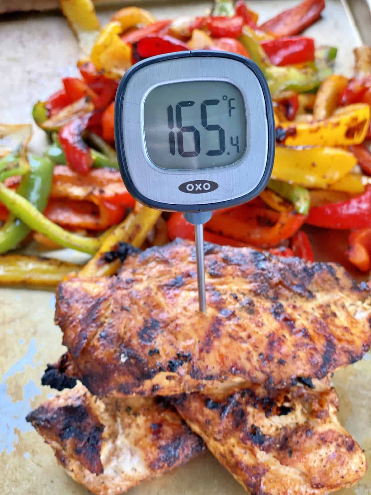 OXO digital thermometer reading 165 degrees Fahrenheit stuck in a chicken breast.