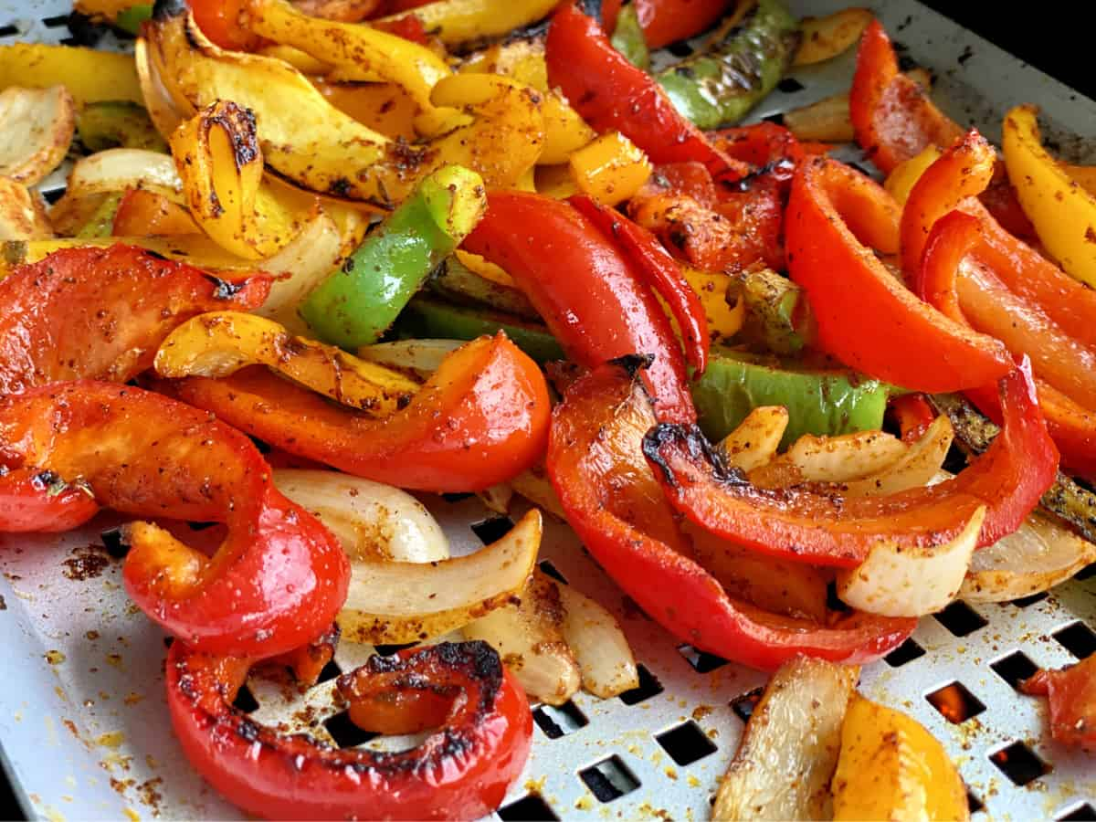 Cooked sliced bell peppers and onions on a silver grill pan.