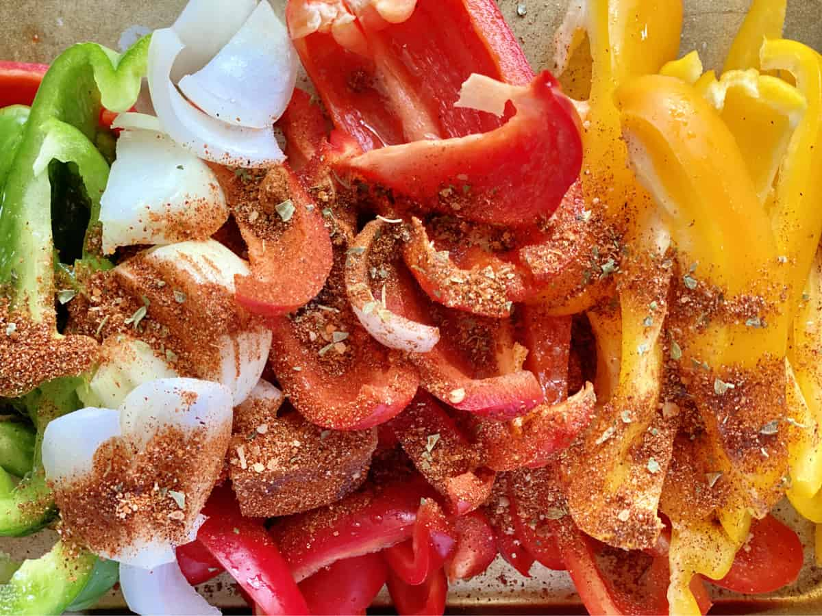 Top view of cut bell peppers and onions with seasoning sprinkled on top.