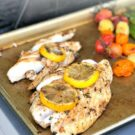 Baking sheet with cooked fish and veggies with text on image for Pinterest.