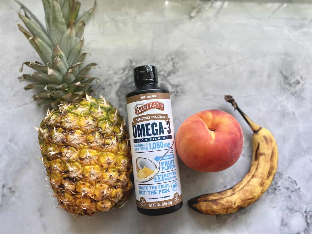 Ingredients on marble countertop: pineapple, Barleans Omega Swirl, Peach, and Banana.