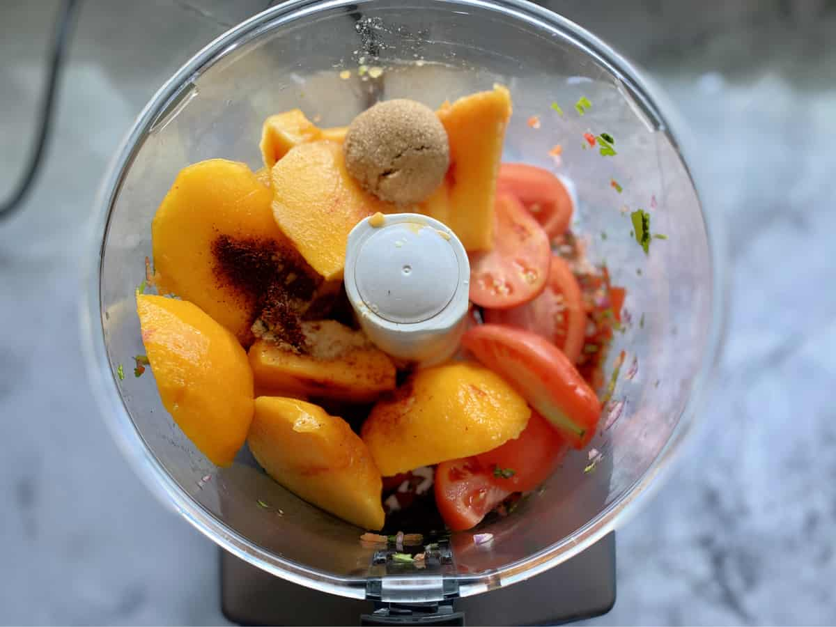 Top view of food processor with peach slices, spices, brown sugar, and plum tomatoes.