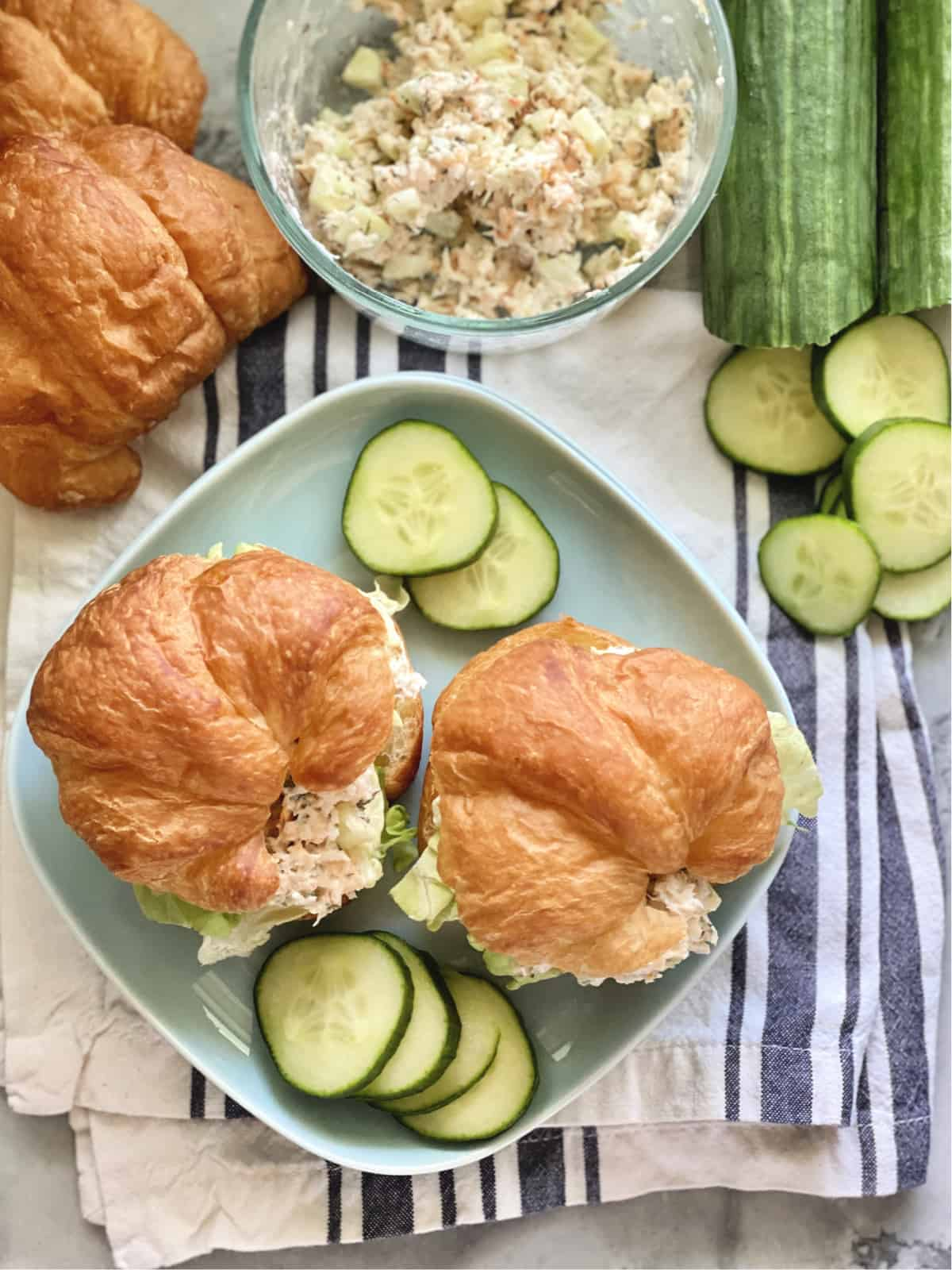Top view of a square blue plate with croissants filled with shrimp salad and cucumber slices.