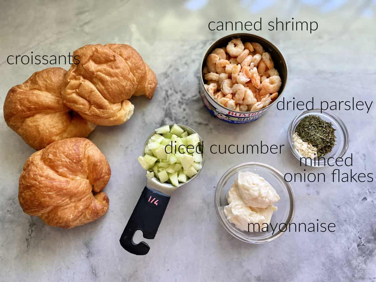 Ingredients on marble countertop: croissants, cucumber, shrimp, parsley, onion, & mayonnaise.