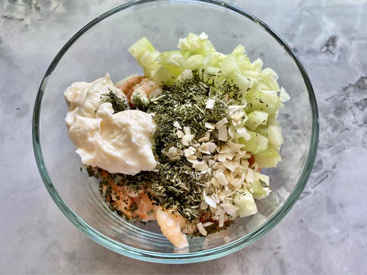 Glass bowl on a marble countertop filled with mayonnaise, shrimp, cucumber, and spices.