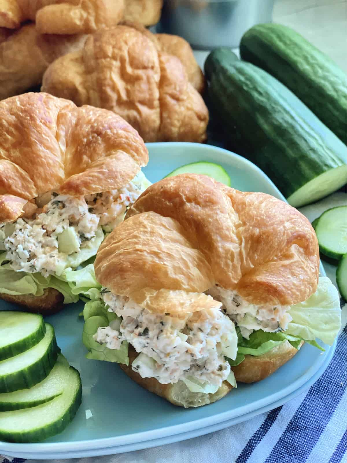 Close up of two croissants filled with seafood salad and lettuce with cucumbers on the side.