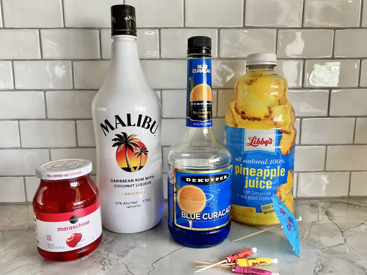 Ingredients; Maraschino cherries in a jar, Malibu rum, Blue Curacao, Pineapple Juice and paper umbrellas.