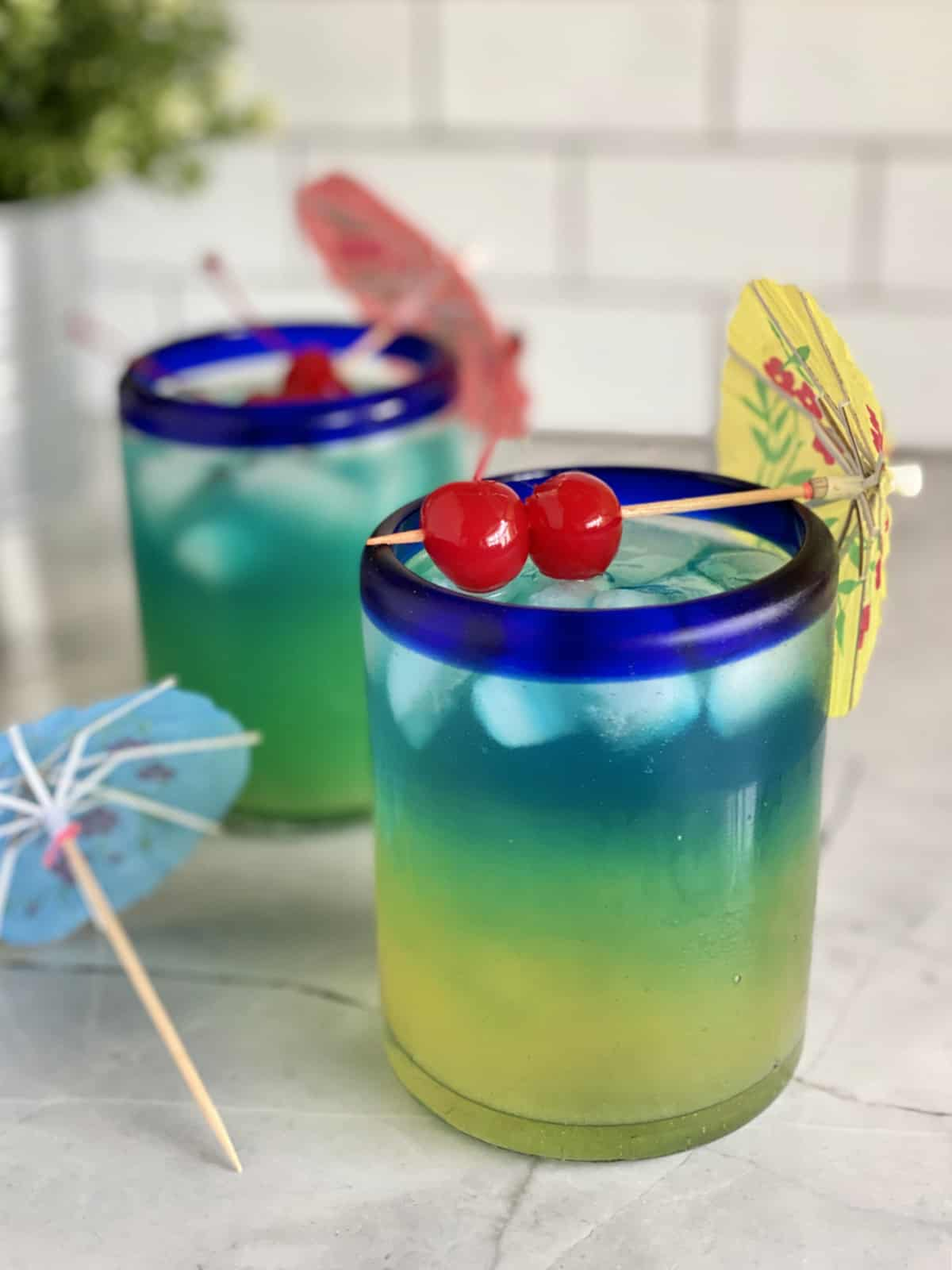 Two drinks that are yellow, green, blue with 2 maraschino cherries on top with a paper umbrella.
