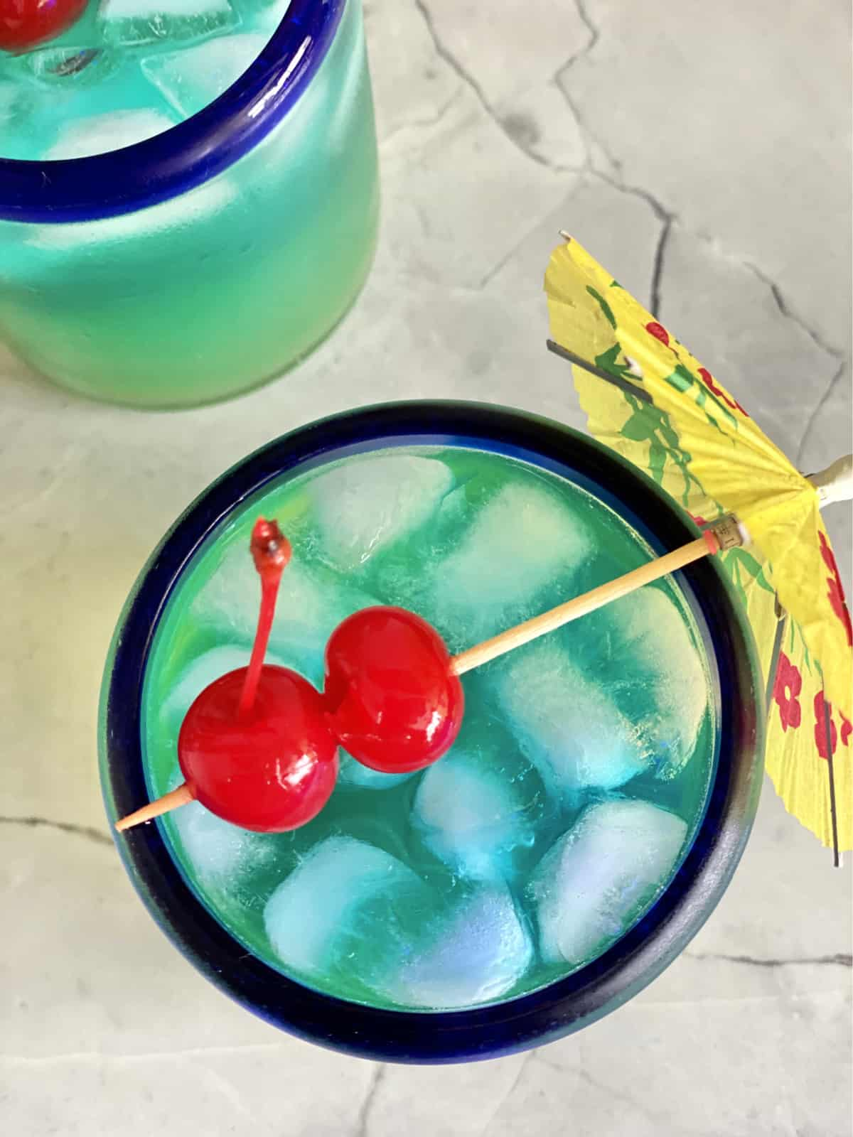Top view of a blue drink with 2 maraschino cherries on top strung through a paper umbrella.