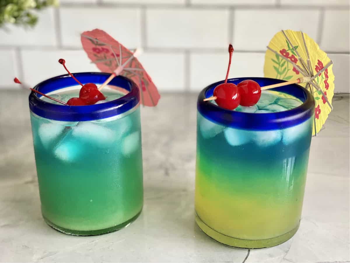 Two drinks side by side one blended light blue color the other layered yellow, green, blue.