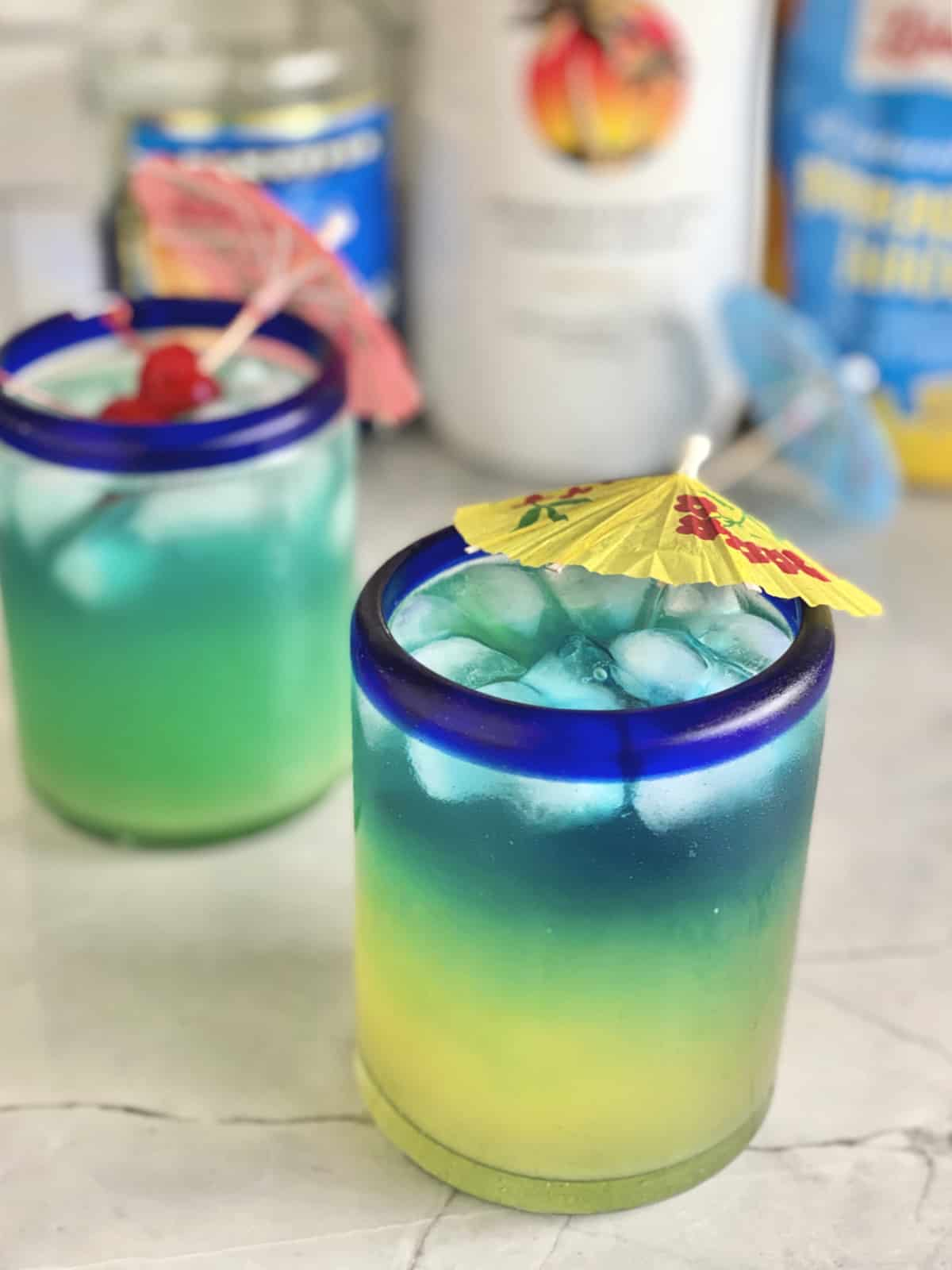 Two blue drinks with paper umbrellas and cherries in the drink.