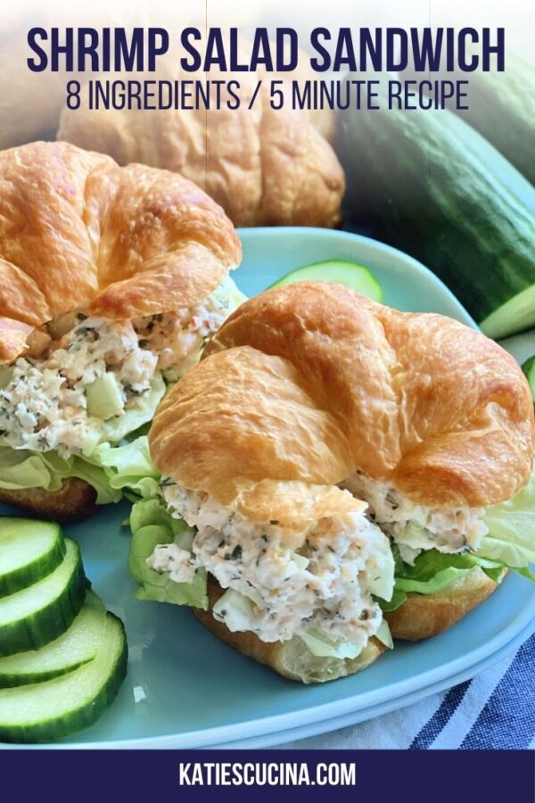 Two shrimp salad croissants on a blue square plate with cucumber slices.