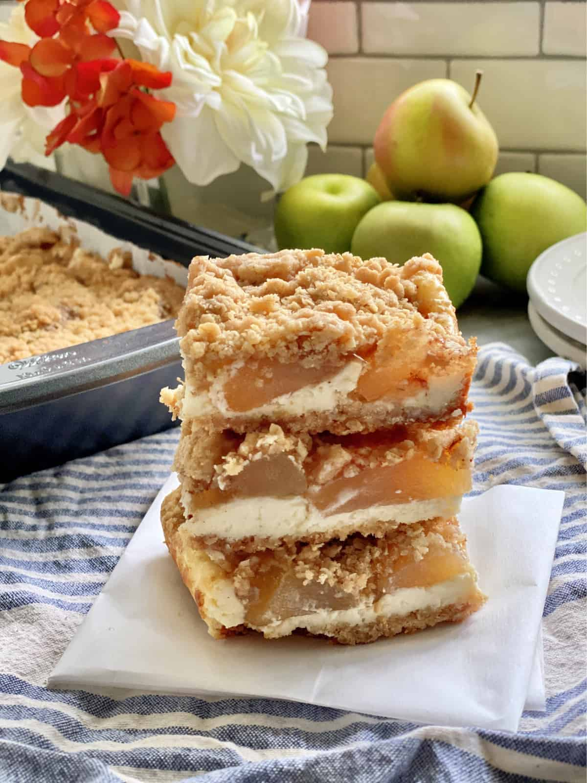Three cheesecake bars filled with apple sitting on a piece of parchment paper.