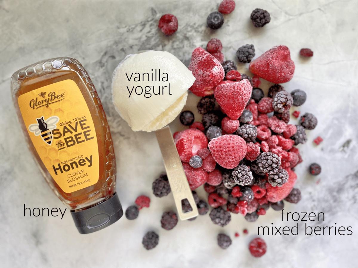 Ingredients on marble countertop: frozen mixed berries, vanilla yogurt, and honey.