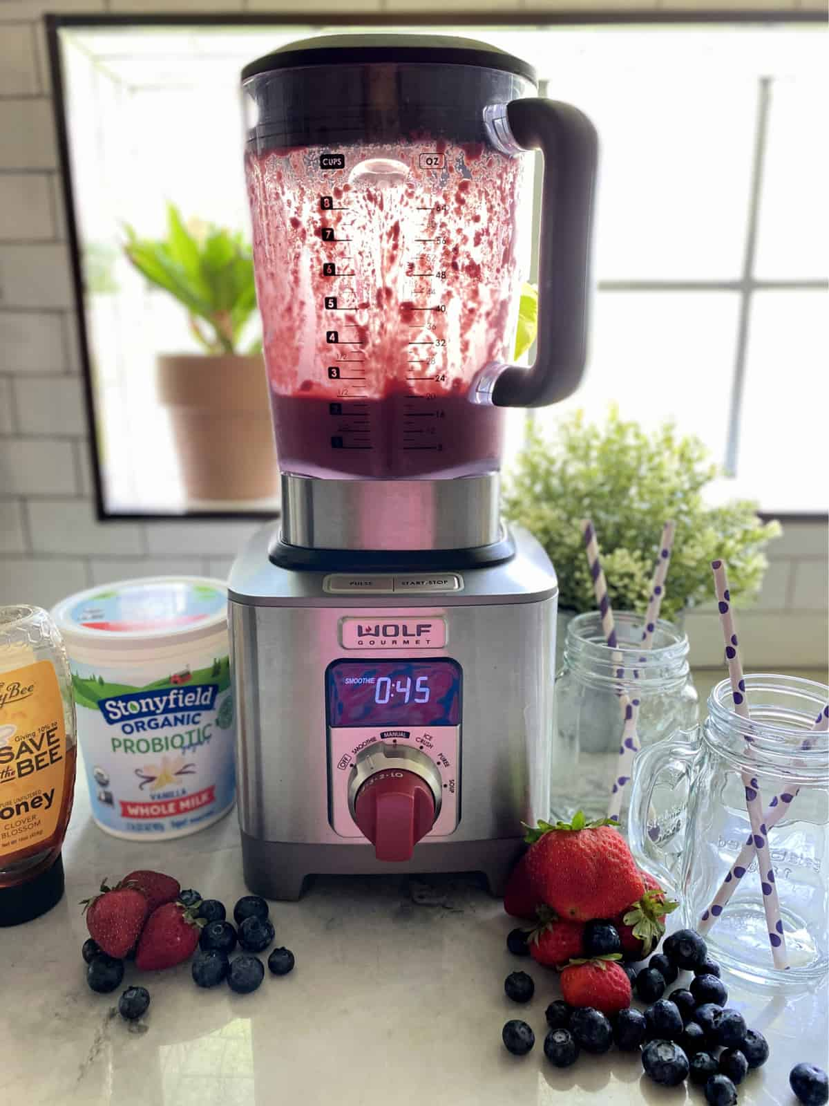 Wolf gourmet blender with purple smoothie in blender, clear glasses and ingredients next to blender.