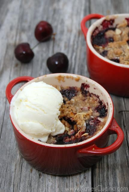 Two red mini ramekins with cherry crisp and a scoop of vanilla ice cream.