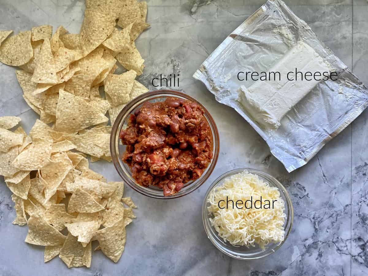 Ingredients on marble countertop: tortilla chips, chili, cream cheese, cheddar cheese.