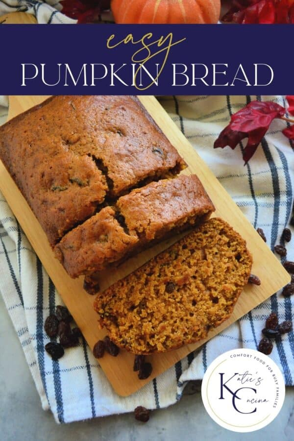 Top view of pumpkin bread with raisins on cutting board with 2 slices cut with text on image.