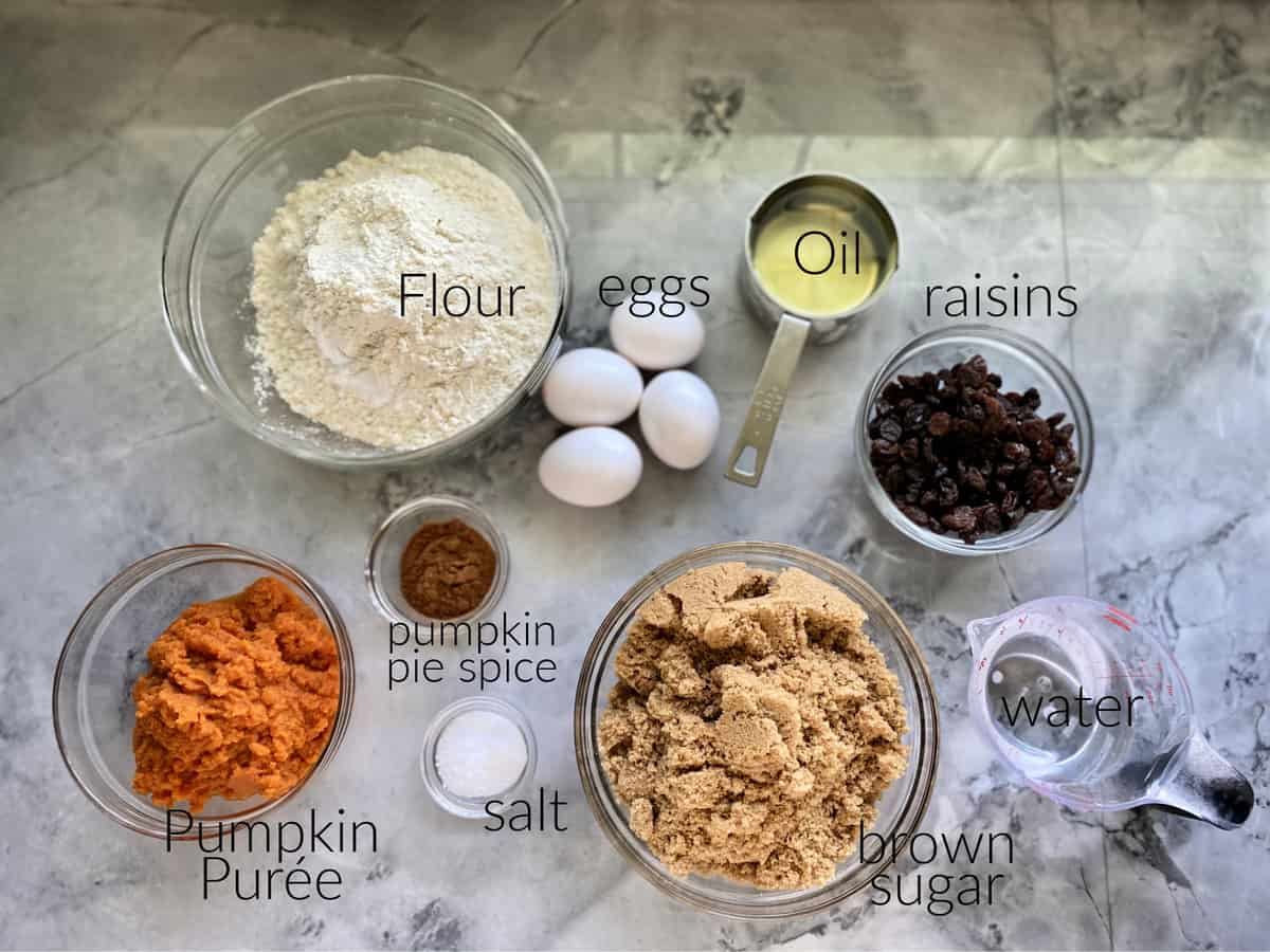 Ingredients on counter: flour, eggs, oil, raisins, pumpkin puree, salt, pumpkin spice, sugar.