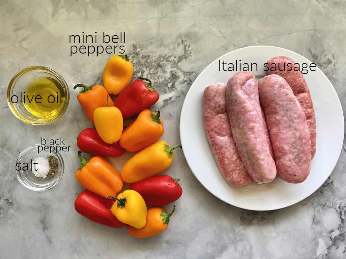 Ingredients on a marble countertop: olive oil, salt, pepper, mini bell peppers, Italian sausage.