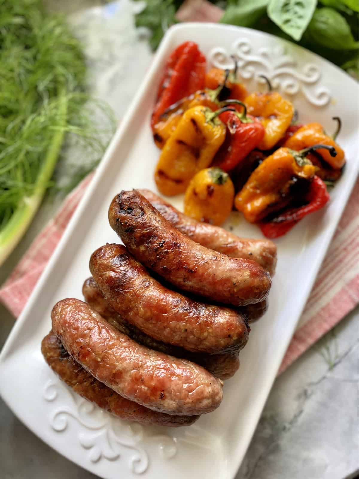 Top view of grilled Italian sausage with charred mini peppers on a white plate with fresh herbs.