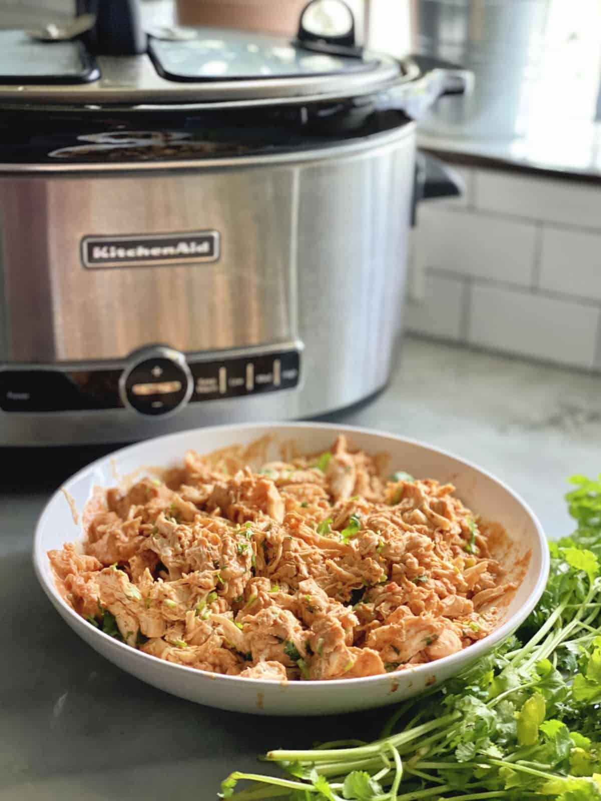 Shredded Chicken with cilantro in a white bowl with slow cooker in background.
