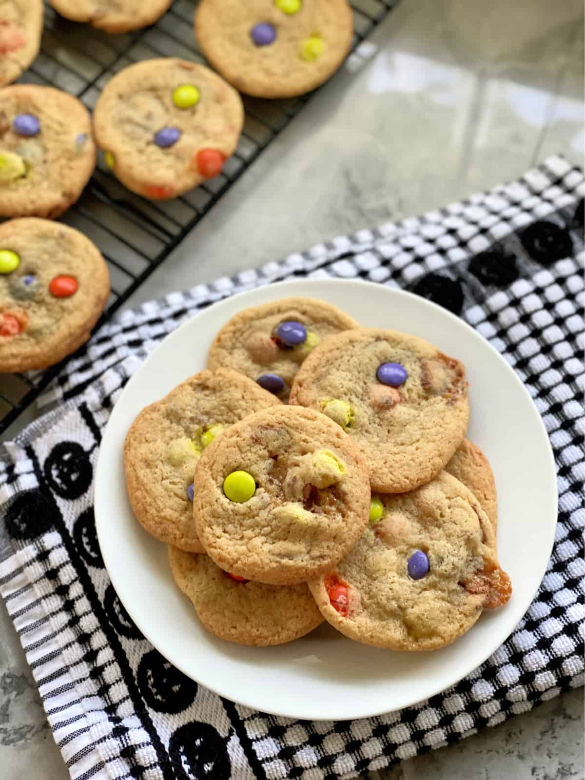 White plate filled with M&M cookies on a black and white dish cloth.